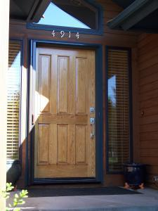 wooden entry door with wood-grain mirage retractable screen installed
