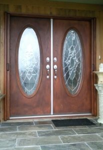 wooden double entry doors with wood grain mirage retractable screens installed