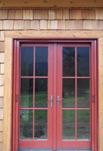 red double entry doors with red retractable screen doors installed